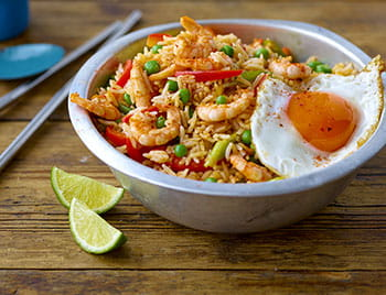 Prawn Fried Rice with fried egg in a bowl with lime and noodle sticks on the side