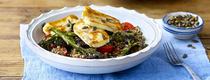 Roasted broccoli and halloumi salad in white bowl on blue cloth