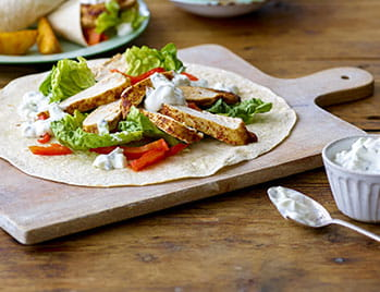 Chicken wrap with garlic yoghurt on a wooden board