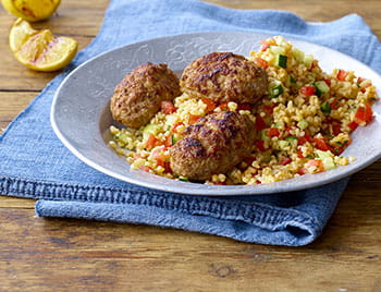 Lamb koftas with bulgur wheat salad on a plate and blue cloth