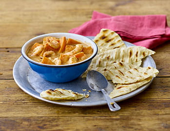 Caribbean curry in blue bowl with roti on the side