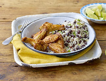 Caribbean jerk wings with rice and peas in a bowl