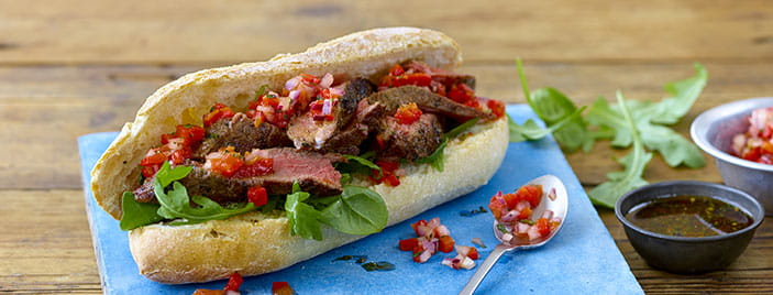 Chimichurri steak sandwich with tomatoes and rocket on a blue surface