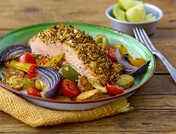 Chimichurri crusted salmon with vegetables in a green bowl and lime on the side