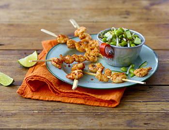 Prawn kebabs with edamame salad on a plate and lime on the side