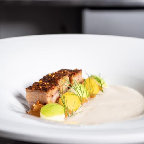 Soupe au chou-fleur confit avec flanc de porc, pommes et fenouil