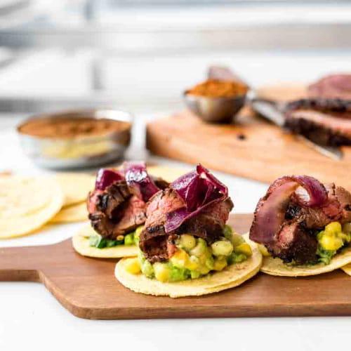 Tacos de bavette, guacamole d'avocat et de maïs sucré, et oignons cubains grillés