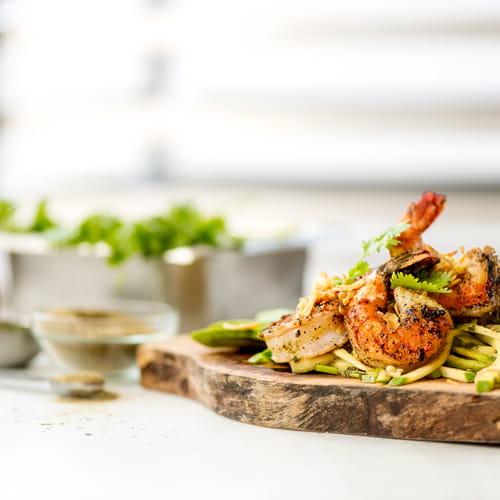 Crevettes grillées au poivre noir avec salade de mangue verte et d'avocat