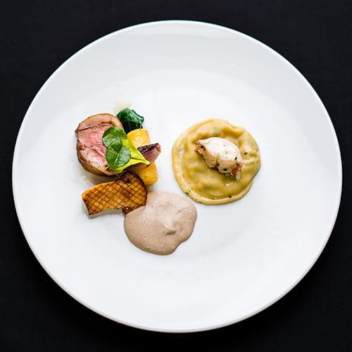 Longe d'agneau rôtie au beurre avec champignons matsutake rôtis, rutabaga confit, échalotes, épinards et raviolis au homard