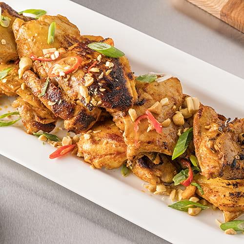 Cuisses de poulet grillées  avec arachides rôties et coriandre