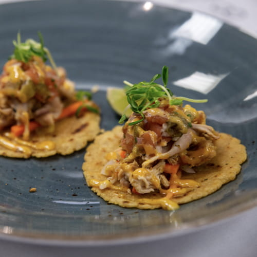 Poulet de Cornouailles grillé à la noix de coco, taco de maïs avec assaisonnement habanero brûlant et ail rôti La Grille, salade de jicama et carottes, salsa aux tomates, aïoli à la lime fraîche