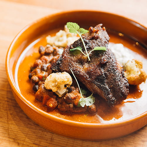 Épaule d'agneau rôti au cumin et au garam masala Club House avec pois chiches noirs et chou-fleur croustillant