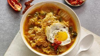 Bol de bouillon au kimchi, accompagné de riz croustillant et d'un œuf au plat